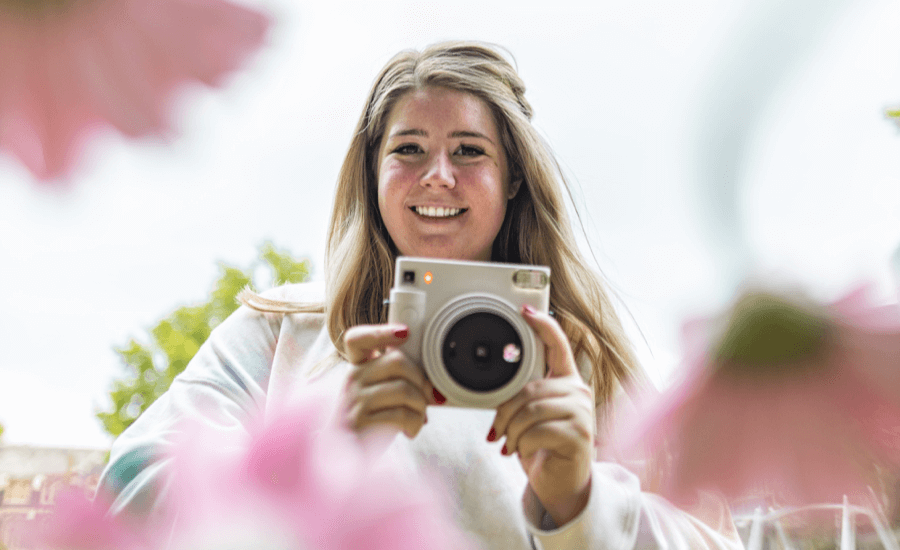 Blonde woman holds a white camera with blurry flowers in the foreground