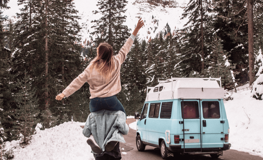 Person on someone's shoulders with a snowy mountain and blue van in the background