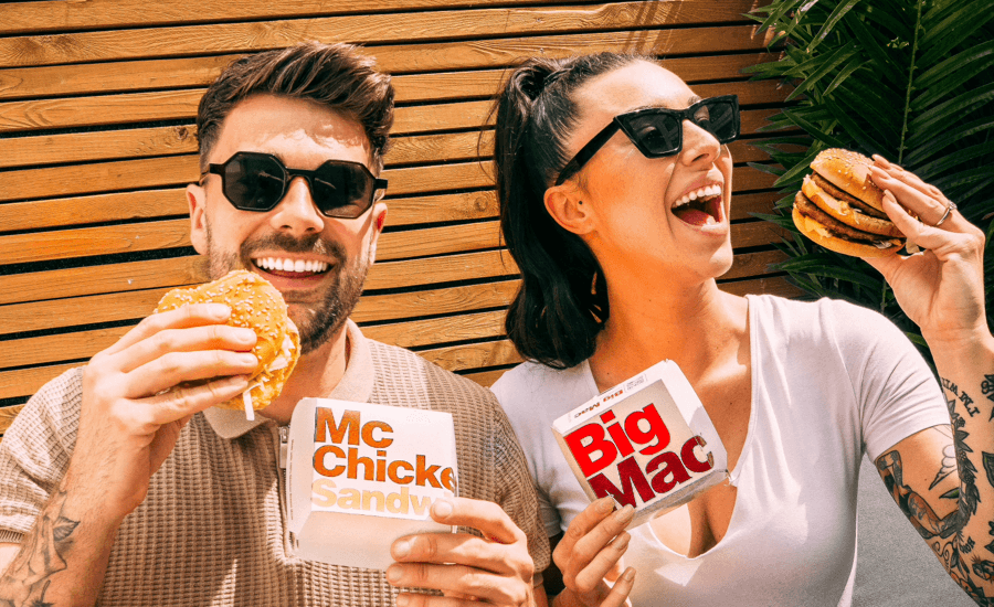A man and a woman holding McDonal's burgers and smiling